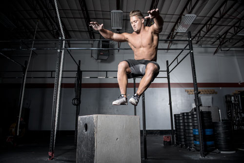 CrossFit Games athlete Sam Dancer at gym working out - performing box jumps
